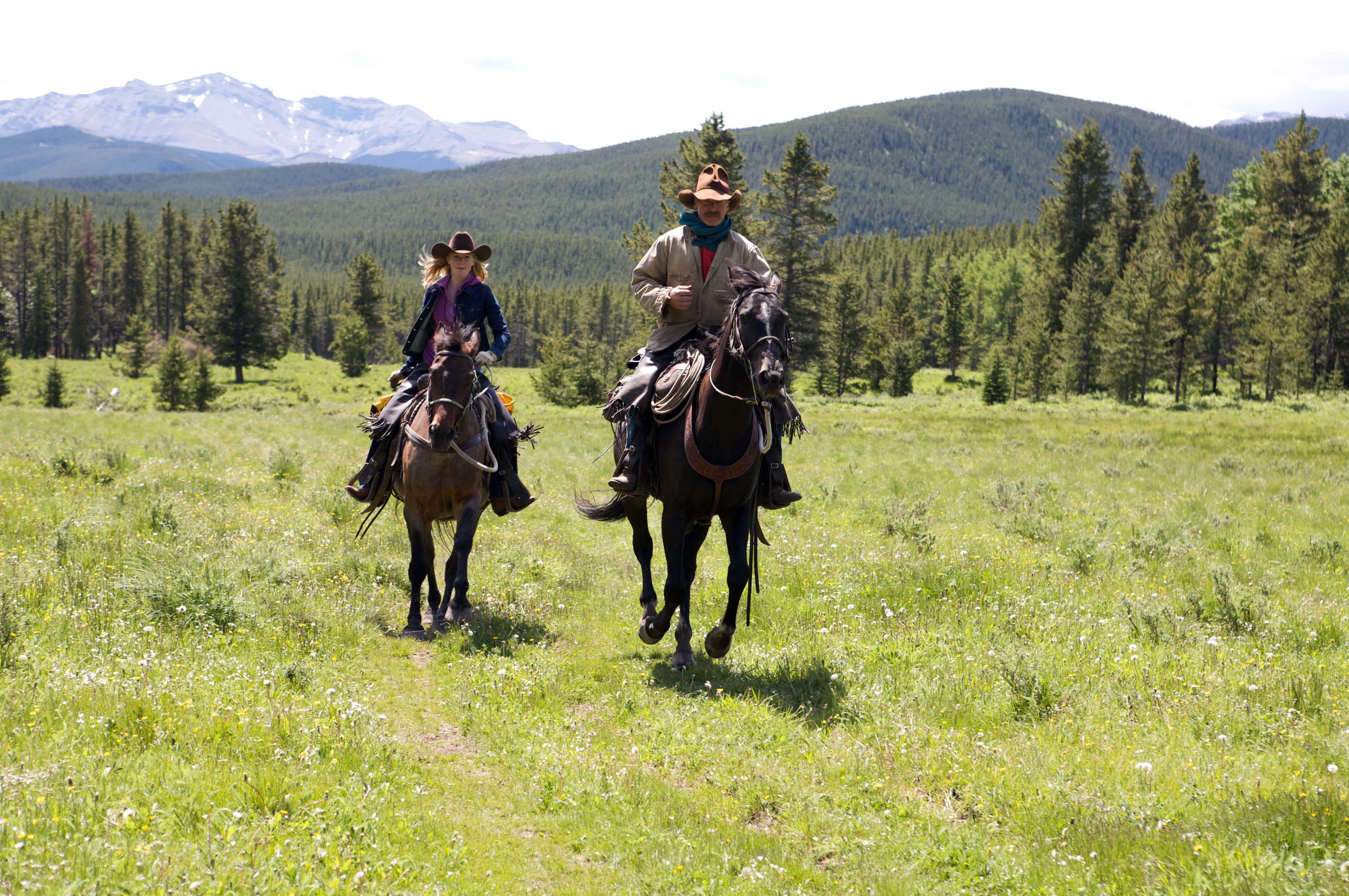 Equitrekking host Darley Newman and outfitter Dewy Matthews canter through the Canadian Rockies, during the filming of Equitrekking Alberta.