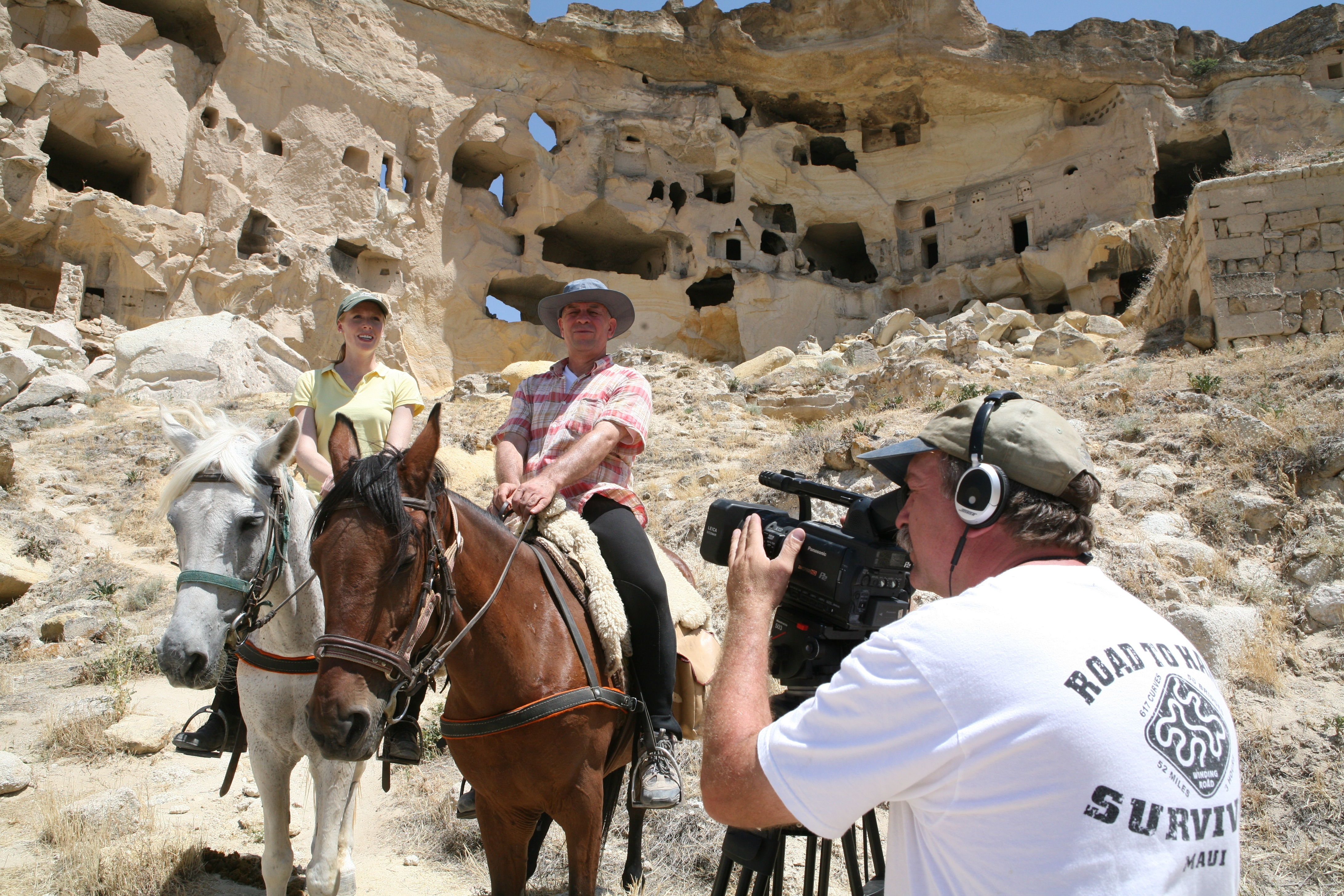 Darley Newman and Ahmet Diler get filmed by Greg Barna in the village of Cavusin in Cappadocia for the Equitrekking Central Turkey. Behind Darley and Ahmet is an old settlement of rock houses, where people lived until the 1950's.