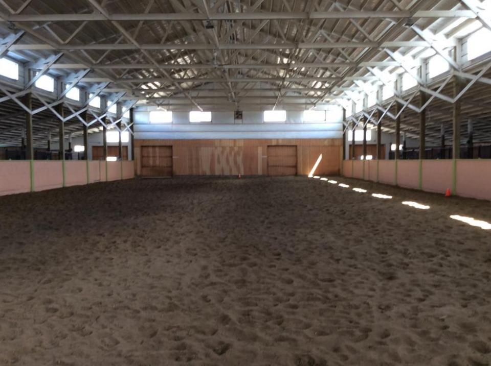 Indoor arena with stalls off of both sides. 12 foot concrete isle ways have tubing in them to heat in winter and cool in summer…with circulating water.
