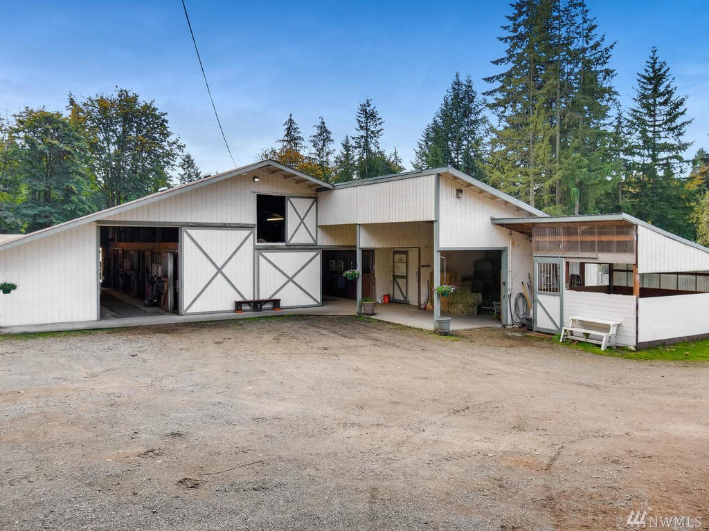 Barn with 21 stalls, hot water wash rack, tack room, feed room, attached shavings bin, and kitchen. Additional outside stall, shavings bin hold 46 yards, large siding feed room door with/man door.