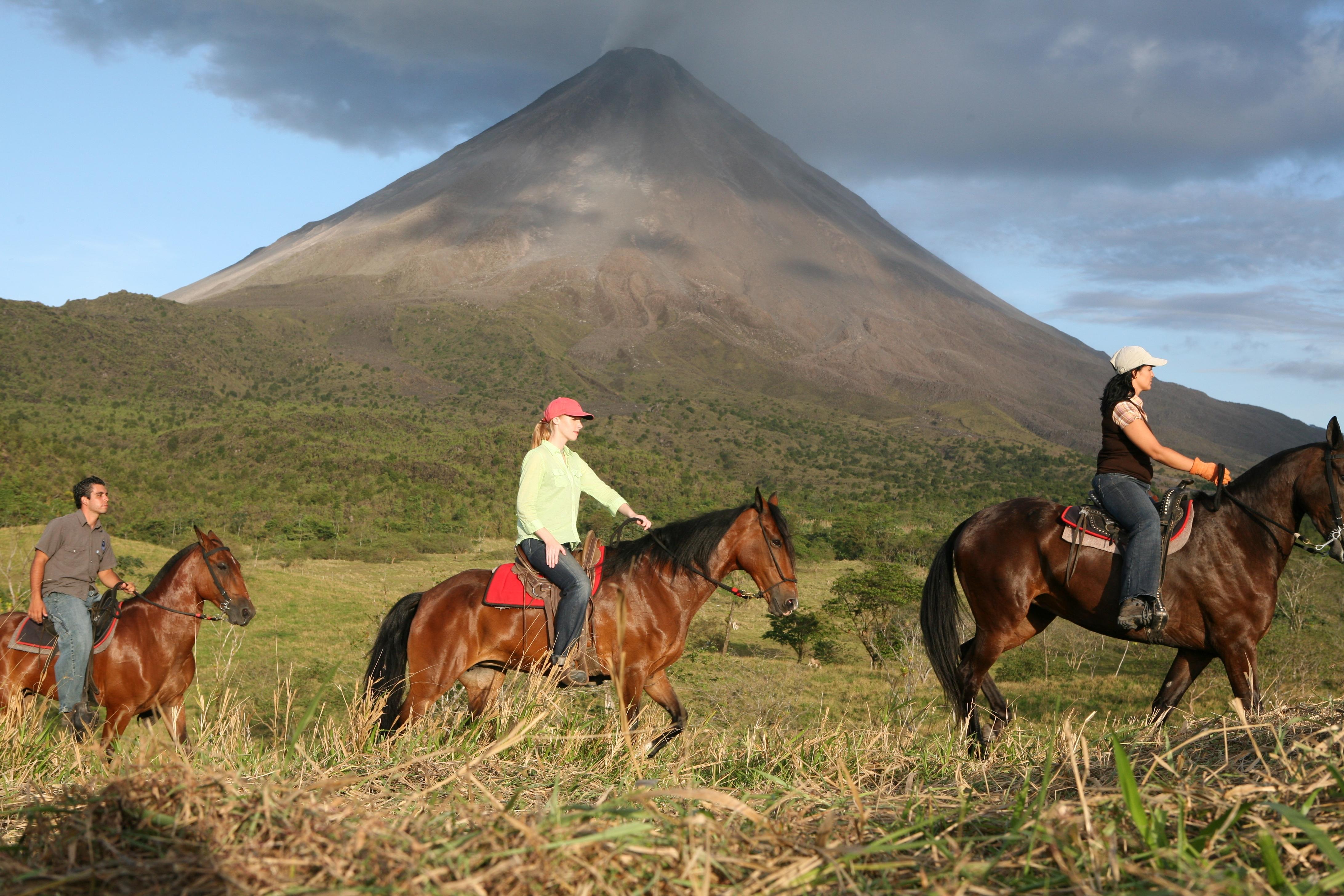 Monica Elizondo, Darley Newman, and Sebastian Mora ride the base of Arenal Volcano  in Costa Rica, as part of Equitrekking Costa Rica.